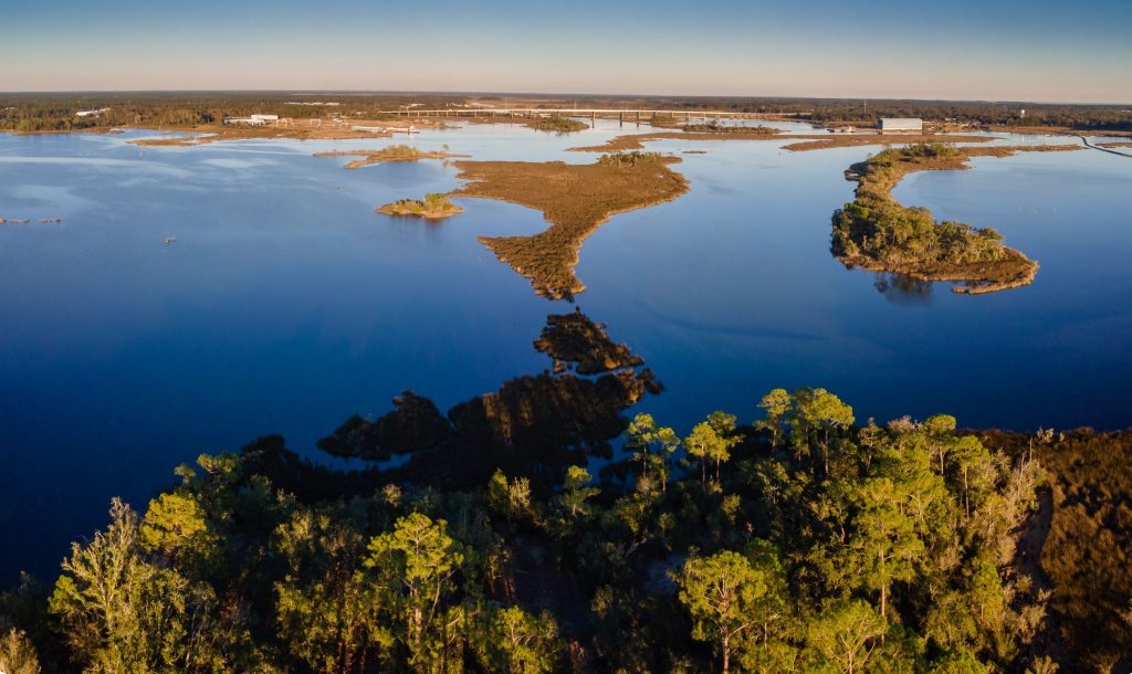 An aerial view of the Moss Point bayou with a bridge in the distance in Mississippi