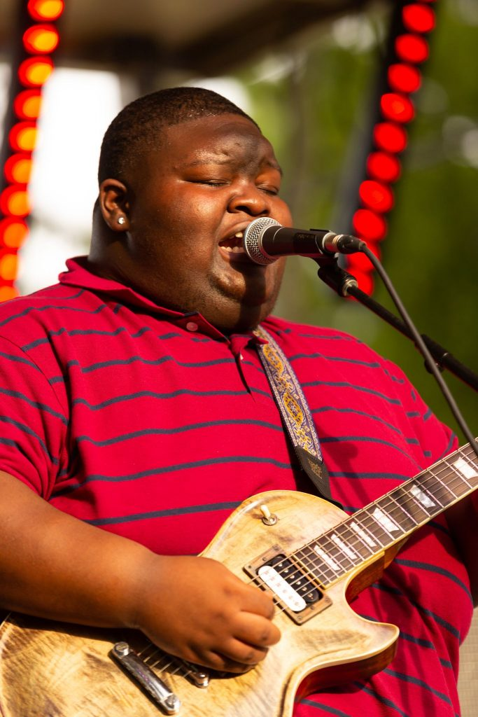 A male singer singing passionately at a blues festival in Mississippi