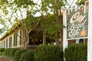 A photo of an exterior of a small business, City Bagel Cafe with green siding and lush green landscaping in Mississippi