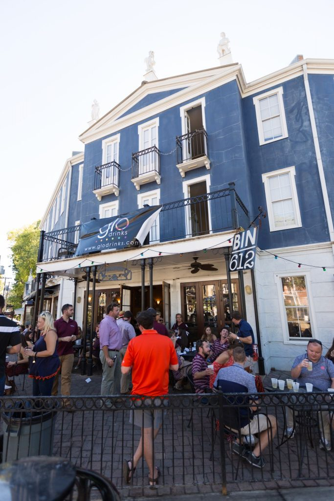 An exterior shot of the Bin 162 restaurant with groups of people sitting at outdoor seating arrangmeents in Mississippi
