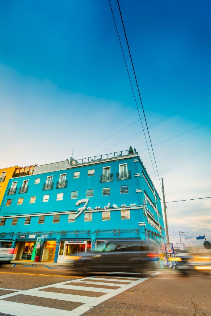A vibrant blue building with Fondren in silver, script font and a blurry car passing by in Mississippi